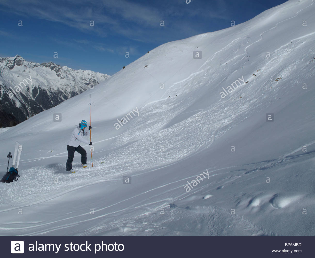 Young woman probing for avalanche victims in winter - Stock Image