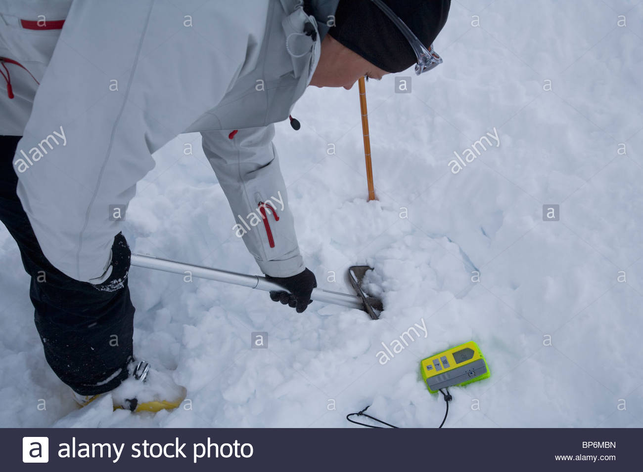 Young woman searching for avalanche victims in snow - Stock Image