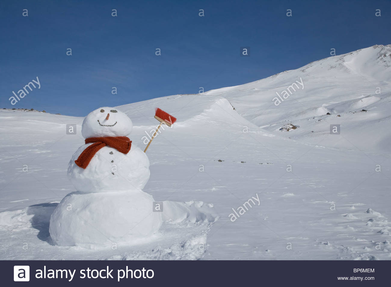 Snowman with broom in mountains on winter day - Stock Image