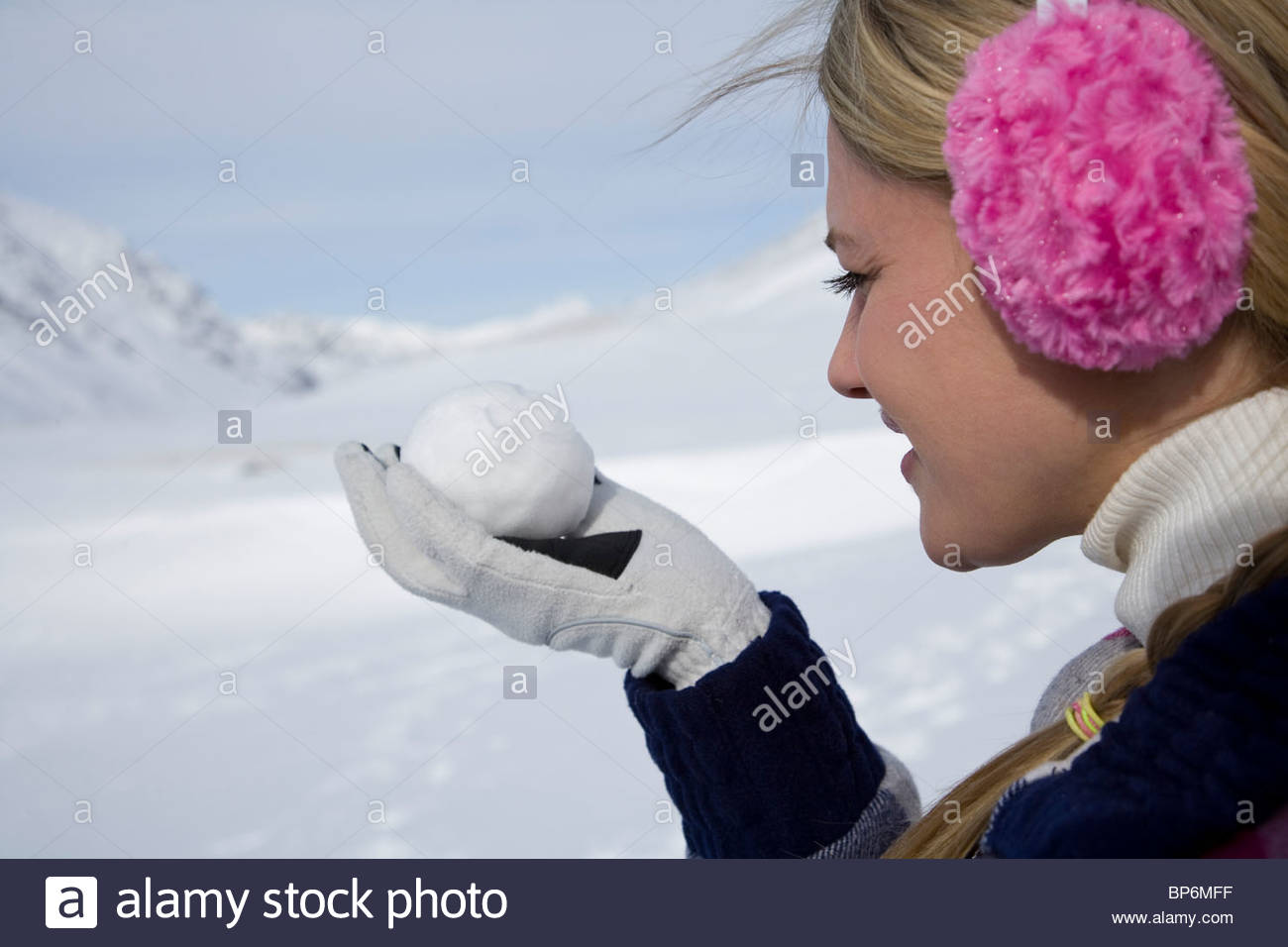 Close-up of young woman holding snowball with smiley face - Stock Image