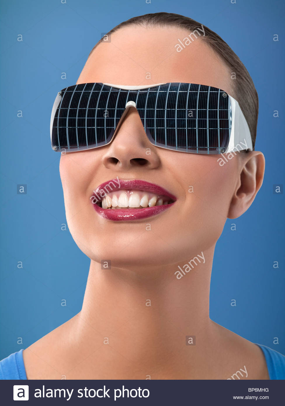 Young woman wearing sunglasses with reflection of solar panels, studio shot - Stock Image