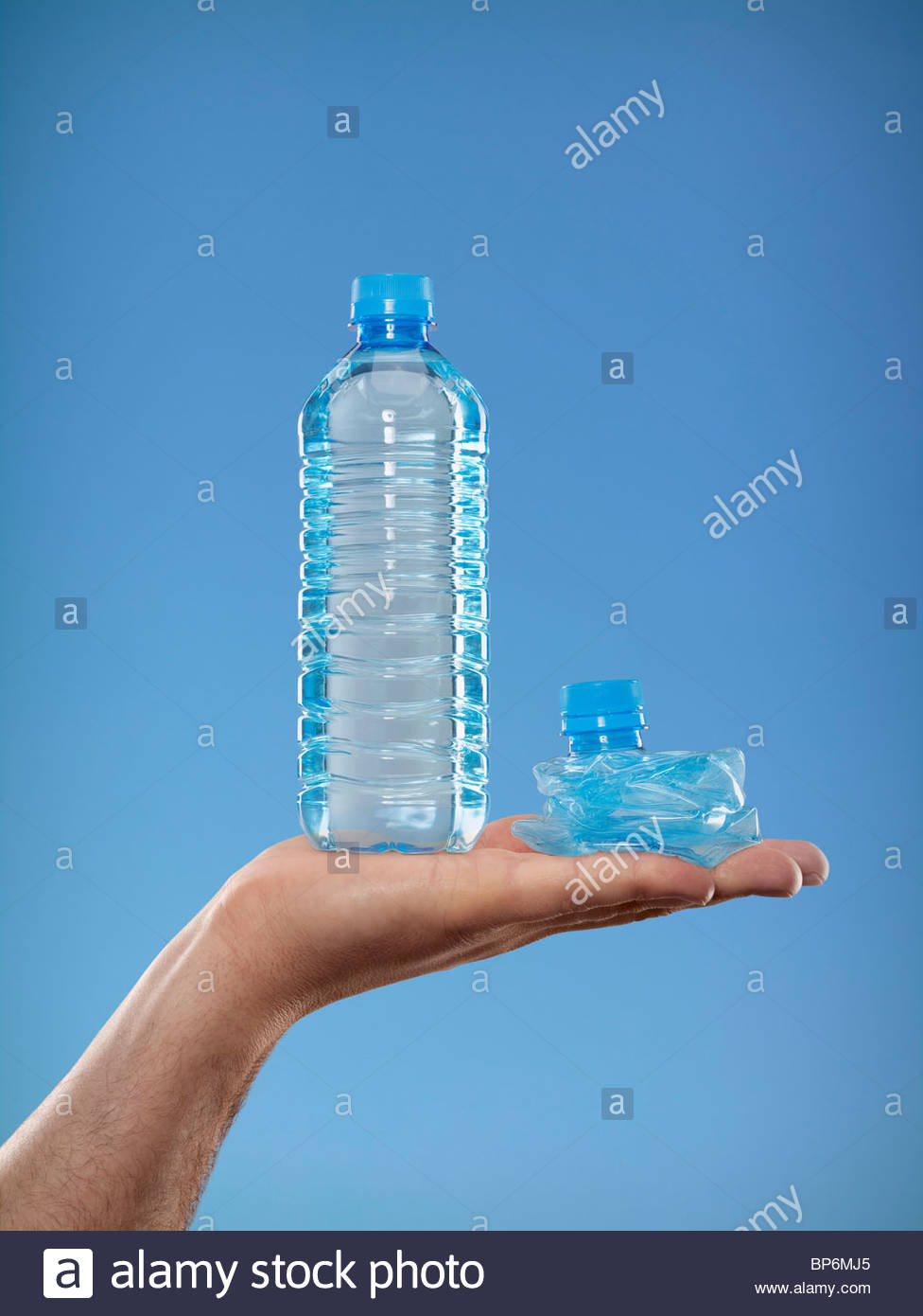 Close-up of man holding full plastic water bottle and crushed bottle - Stock Image