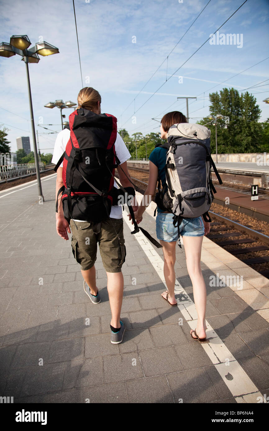 A backpacker couple walking on down a train platform - Stock Image
