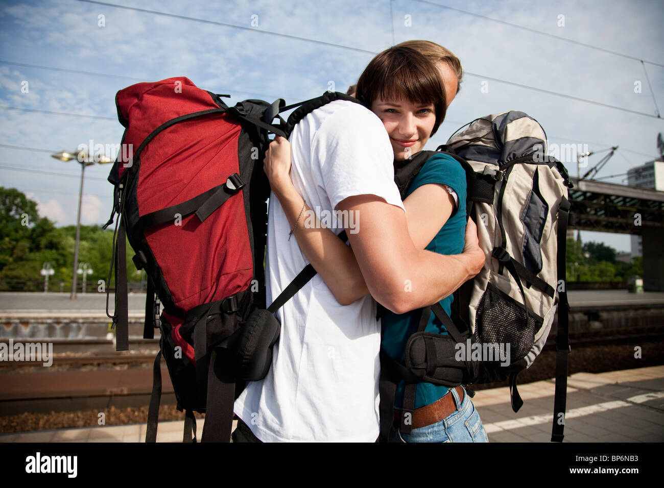 A young woman hugging her boyfriend on a train platform Stock Photo