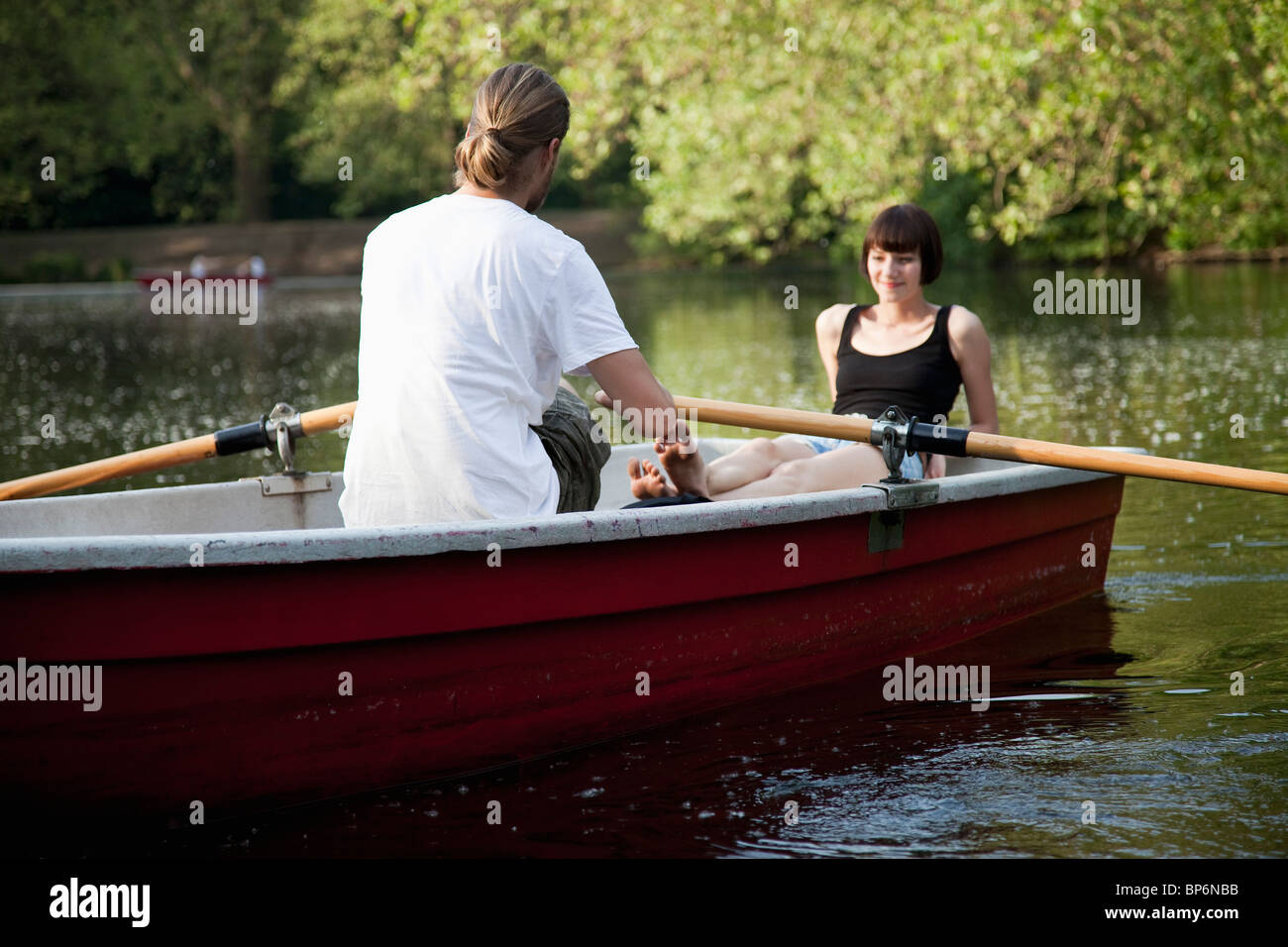 A young couple in a rowboat - Stock Image