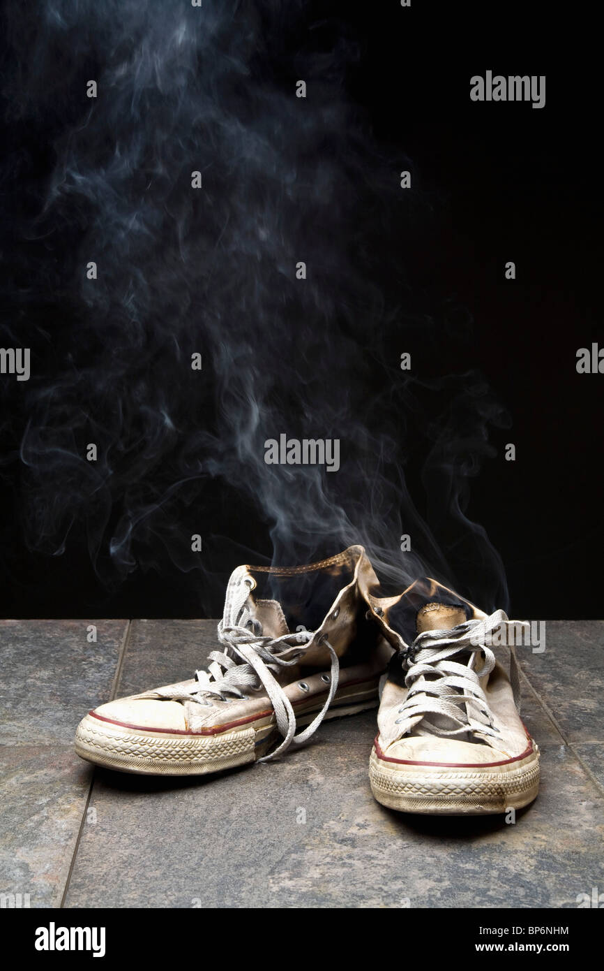 Smoke coming from burnt canvas shoes - Stock Image