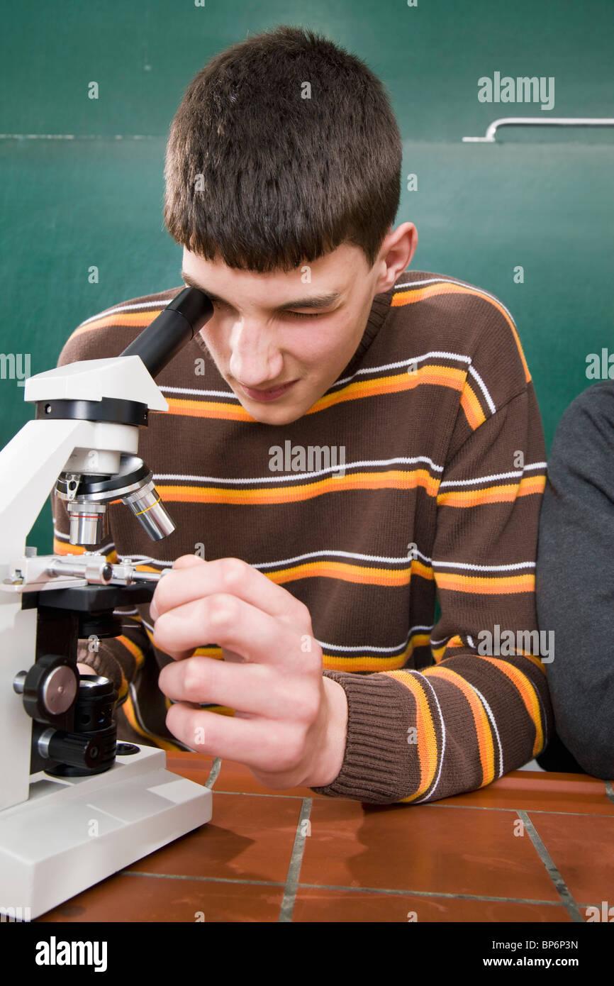 A student looking through a microscope in biology class - Stock Image
