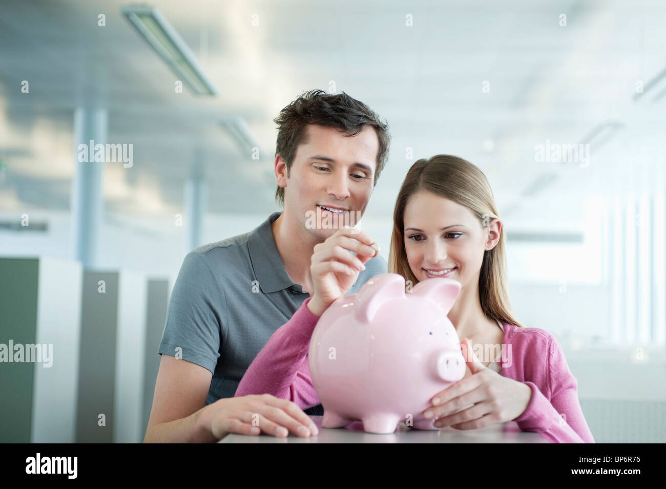 Business executives inserting a coin into a piggy bank - Stock Image