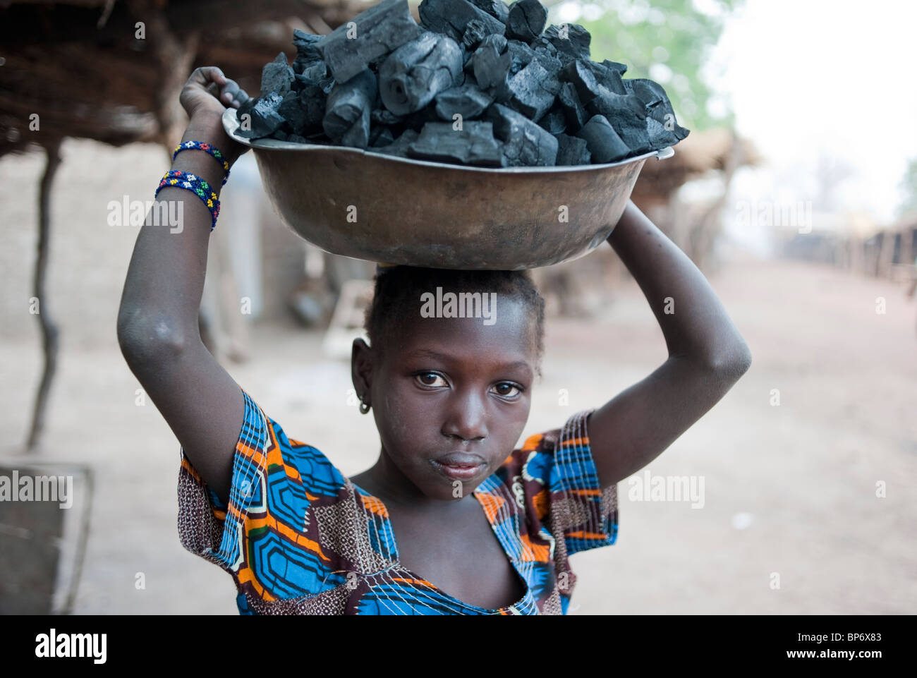 Africa Mali - girl carry charcoal on the head for selling as cooking fuel for kitchen stove - Stock Image