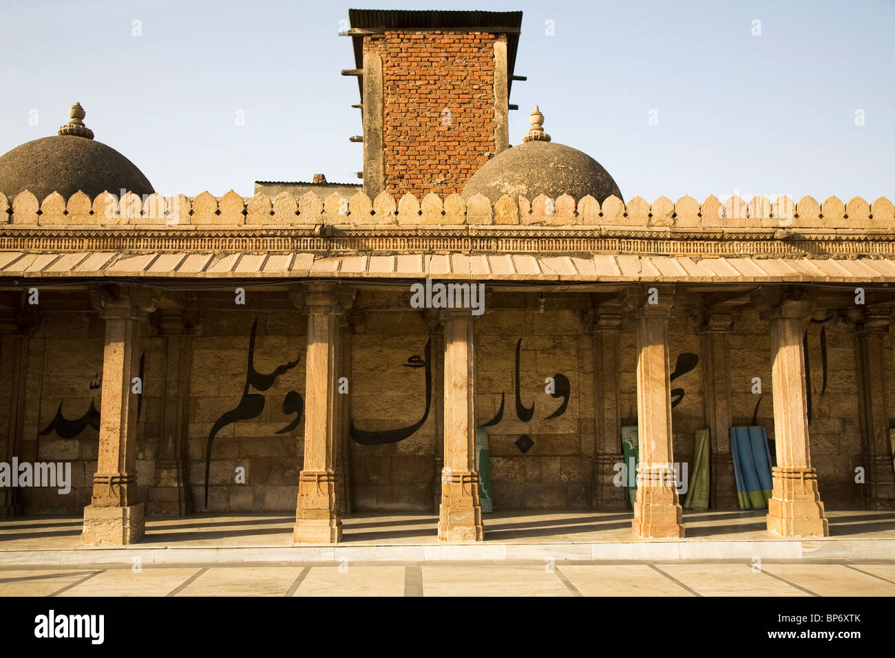 A Koranic inscription runs behind pillars in the Jama Masjid (Friday Mosque) in Ahmedabad, Gujarat, India. - Stock Image