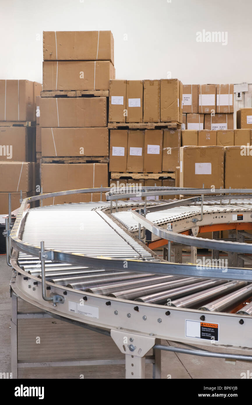 Cardboard boxes and conveyor belt in distribution warehouse - Stock Image