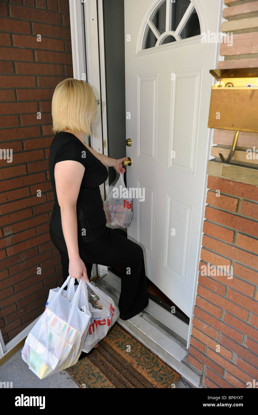 A woman opening a door with groceries in her hand - Stock Image & Grocery Door Stock Photos u0026 Grocery Door Stock Images - Alamy