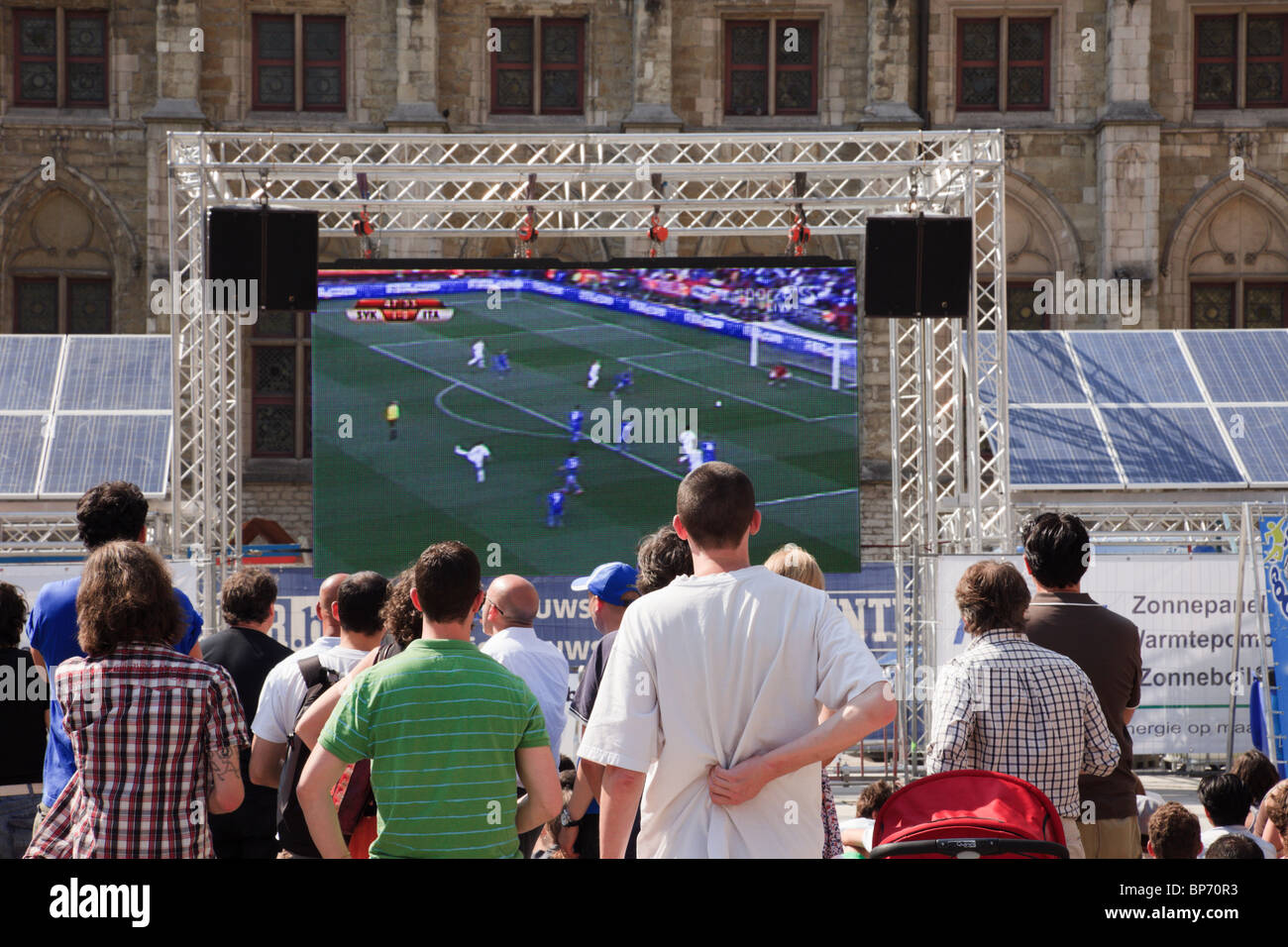 Sint-Baafs Plein, Ghent, East Flanders, Belgium. People outside watching football match on big screen public television - Stock Image