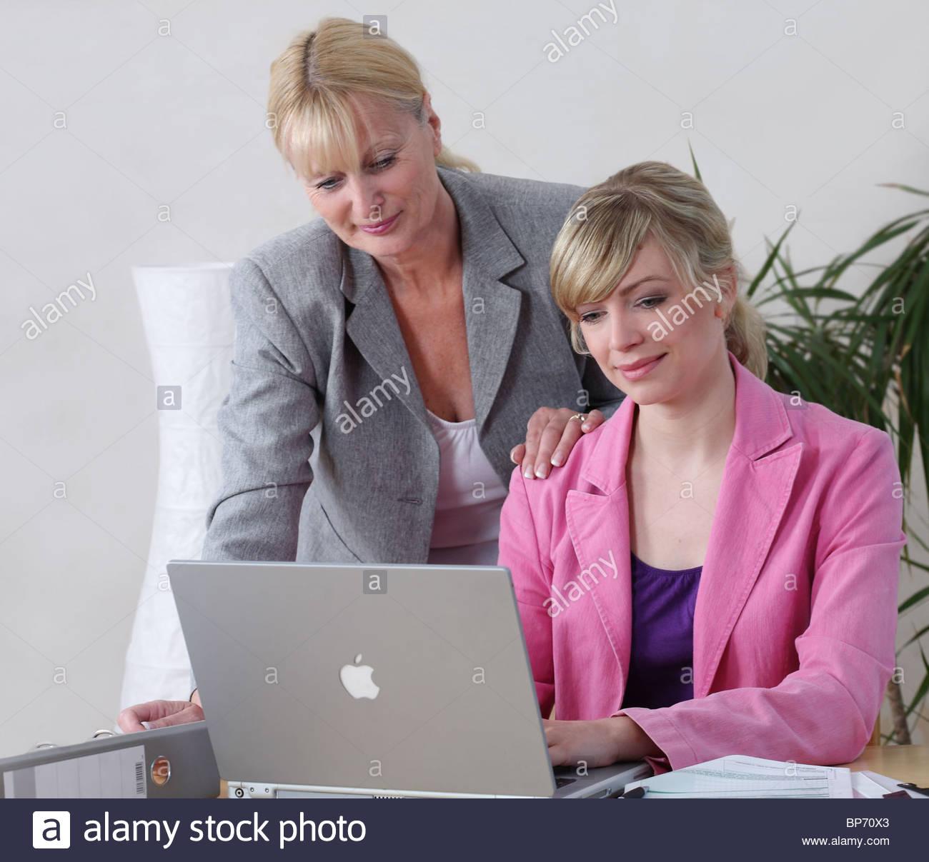 women sitting behind laptop Stock Photo