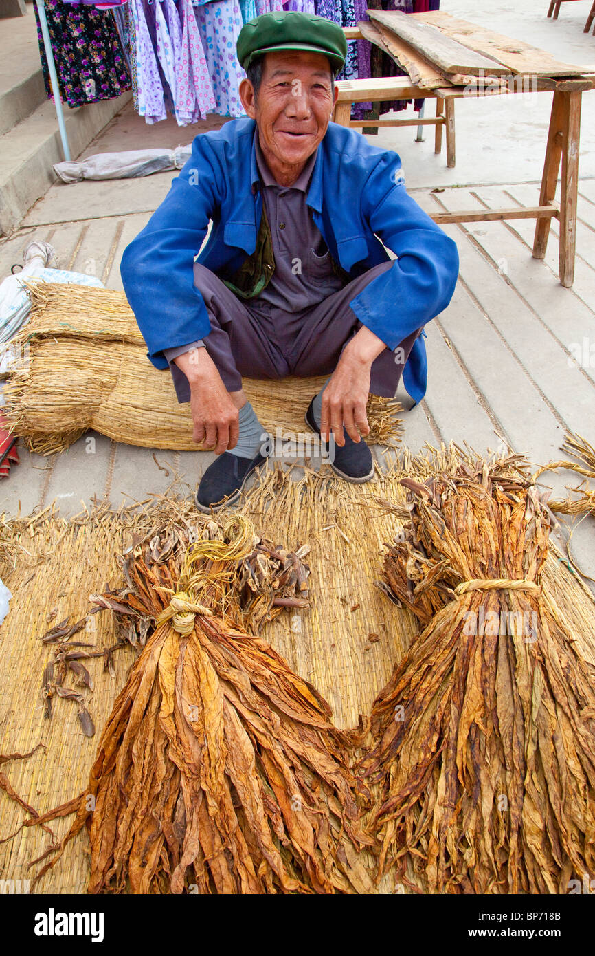 Selling tobacco on market day in Shaxi Village, Yunnan Province, China - Stock Image