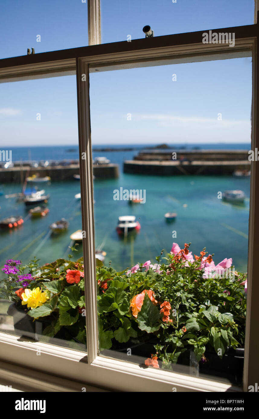 Mousehole harbour seen through a window with flowers in a window box. - Stock Image