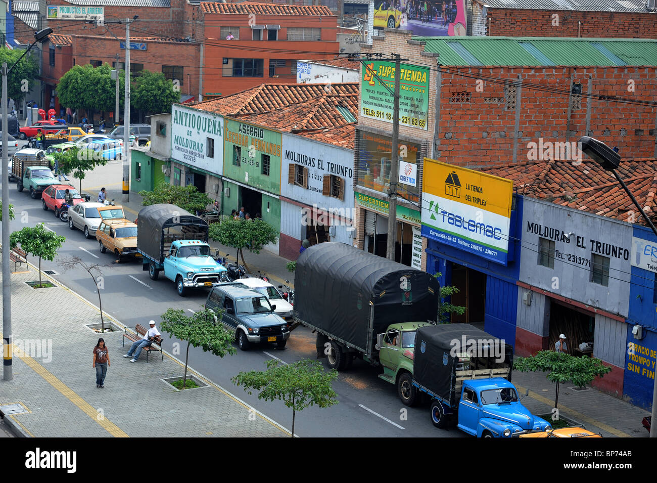 Traffic and parked vehicles on road outside stores in Medellin, South America - Stock Image