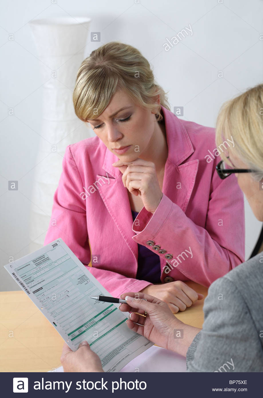women sitting on table discussing holding blank form Stock Photo