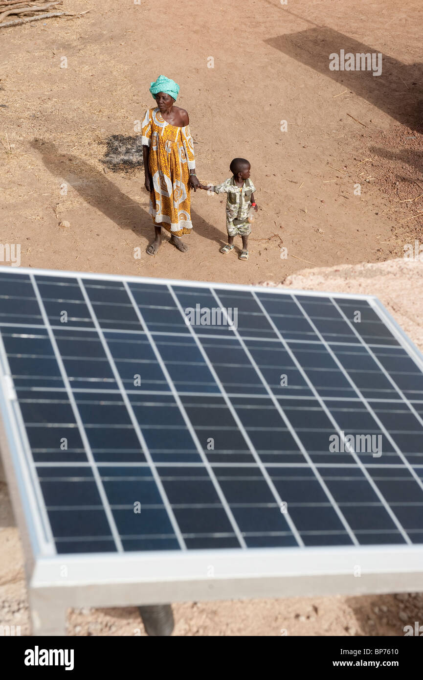 West Africa Mali , solar panel on rooftop of solar powered battery recharge station in village Dialkoro , woman - Stock Image