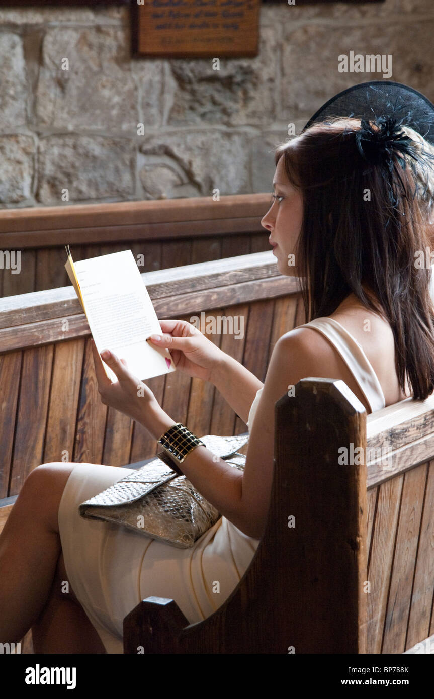 female guest wearing a fascinator at a wedding in church reading from order of service sheet - Stock Image