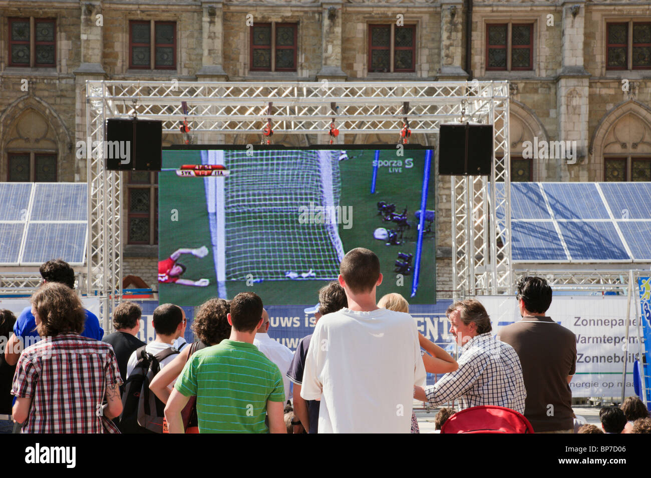 Ghent, East Flanders, Belgium. People outside watching a football match on solar powered big public television screen - Stock Image
