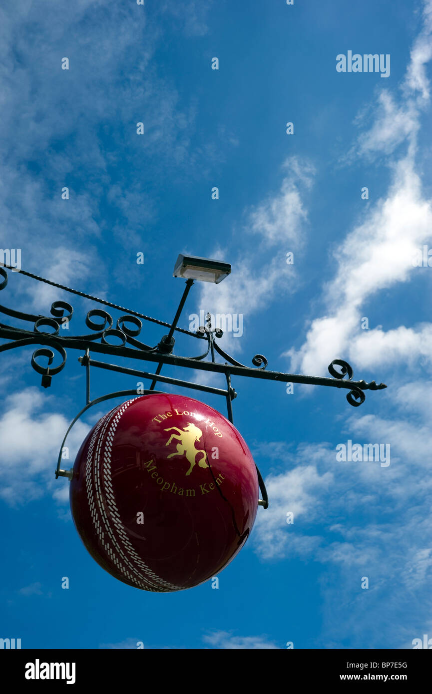 Cricket ball suspended against a Summer blue sky  the hanging pub sign of the Long Hop public house in Meopham Kent - Stock Image