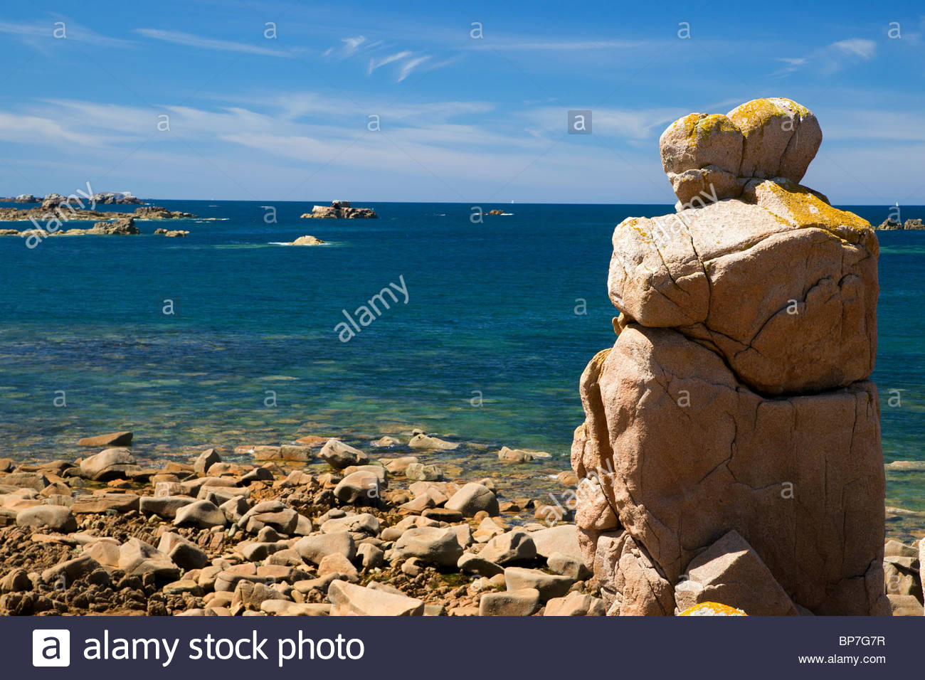 Pink granite rock looking like a human couple standing in front of the sea at Plougrescant - Brittany - France - Stock Image