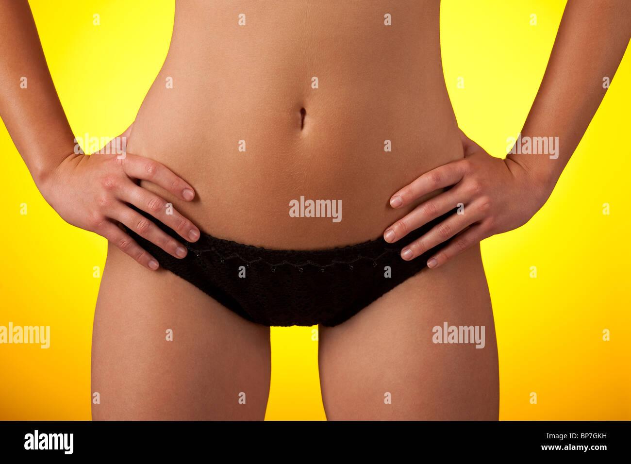 Part of female body wearing black bikini on yellow background - Stock Image