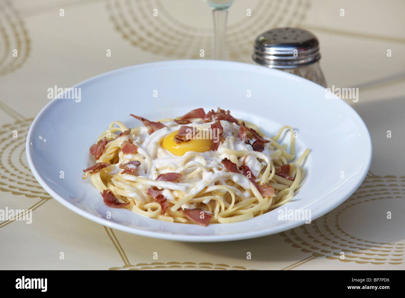 plate of linguine with bacon and fried egg - Stock Image