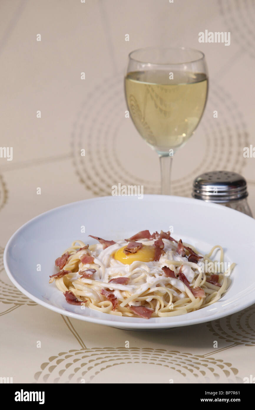 plate of linguine with bacon and fried egg and glass of white wine - Stock Image