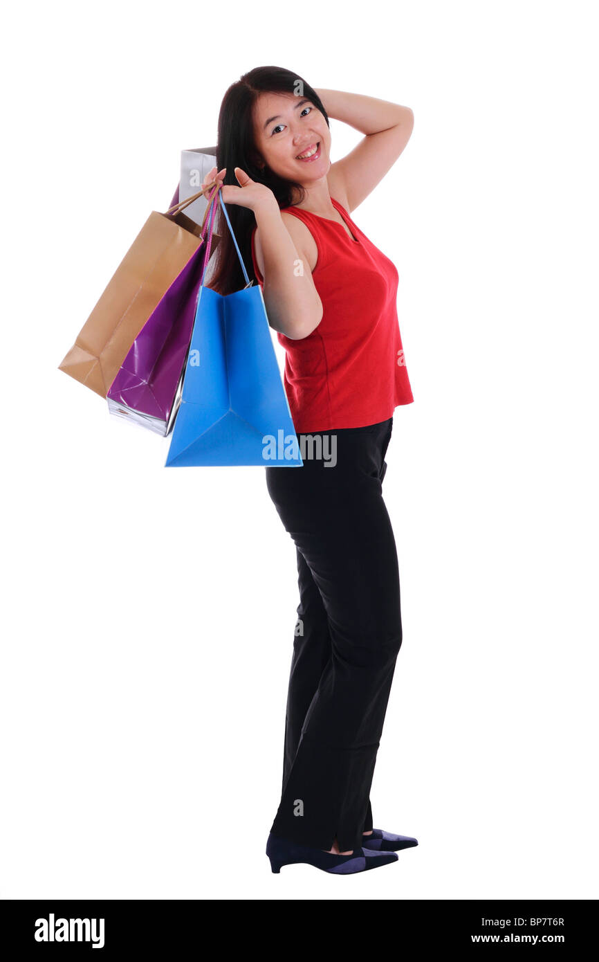 An Asian woman holding multiple shopping bags isolated in white background Stock Photo