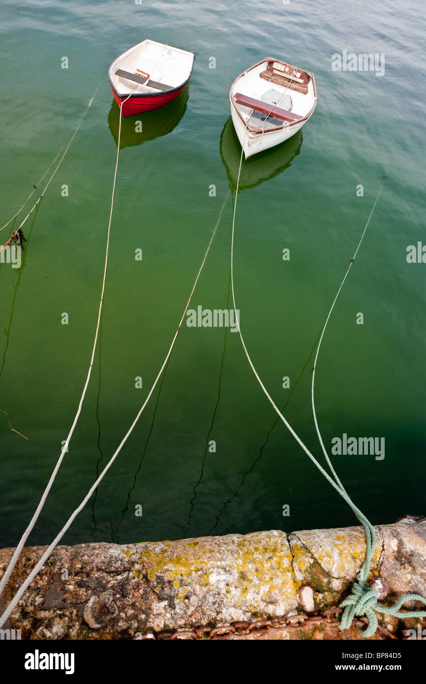 Two Dingies on green water. Two small dingies tied up to a stone wharf in Falmouth's small boat harbour. - Stock Image