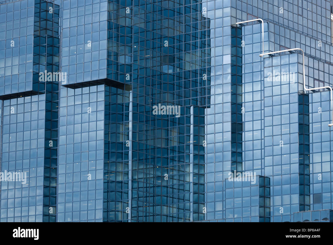 Glass towers of London. Blue reflective glass and a repetitive array of windows forms the facade of this massive - Stock Image