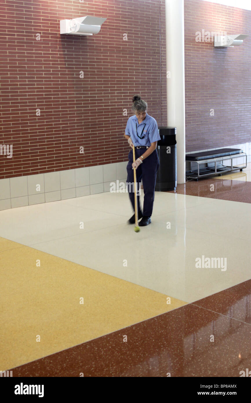 Worker keeping floors spotlessly clean, Blue Heron service plaza ...
