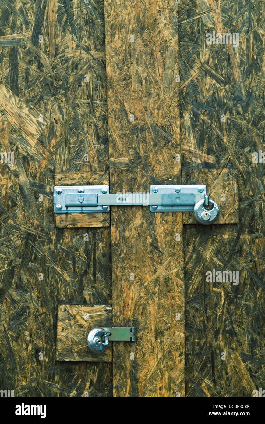 Wooden door secured with two padlocks - Stock Image
