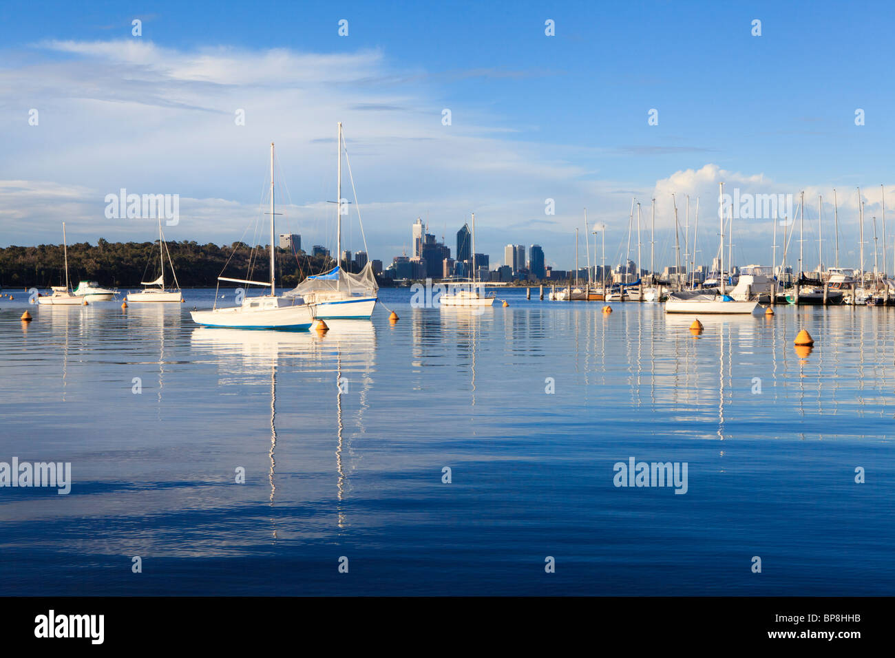 Yachts moored at Matilda Bay on the Swan River, with Perth's skyscrapers in the distance. Stock Photo
