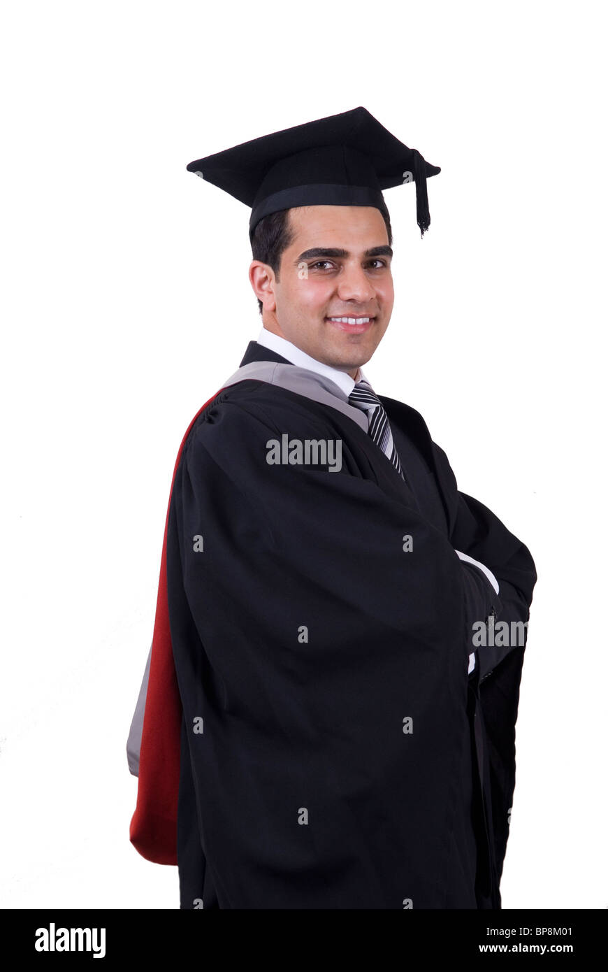 Proud university student wearing cap and gown arms folded standing against a white background - Stock Image