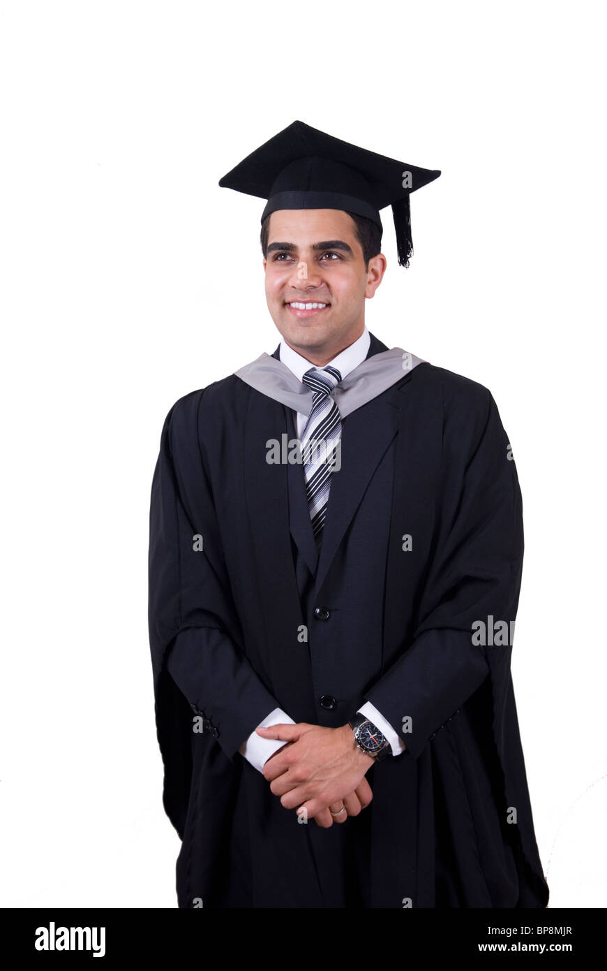 Young Asian university student wearing cap and gown looking up - Stock Image
