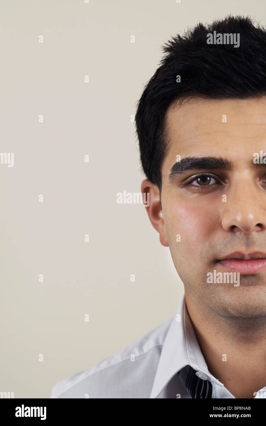 Closeup of a young Asian business man looking at camera - Stock Image