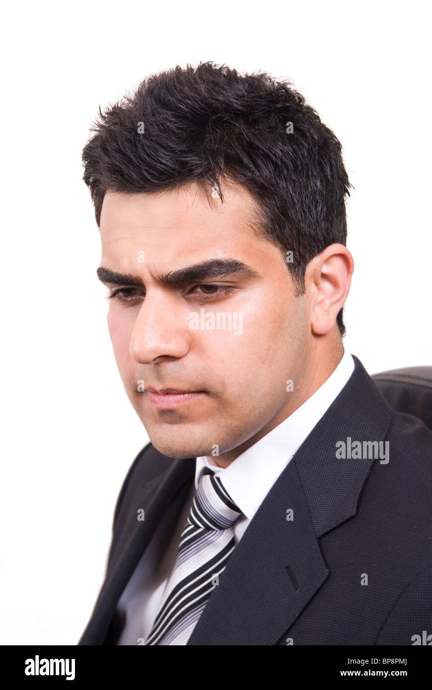 Portrait of a serious Middle Eastern business man thinking against a white background - Stock Image