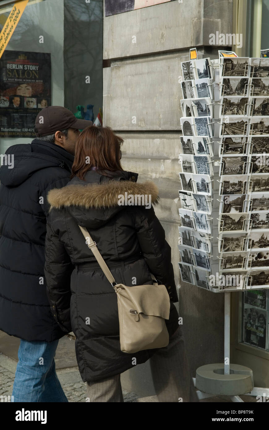 Man and woman looking at postcards stand outside souvenir shop Berlin Germany - Stock Image