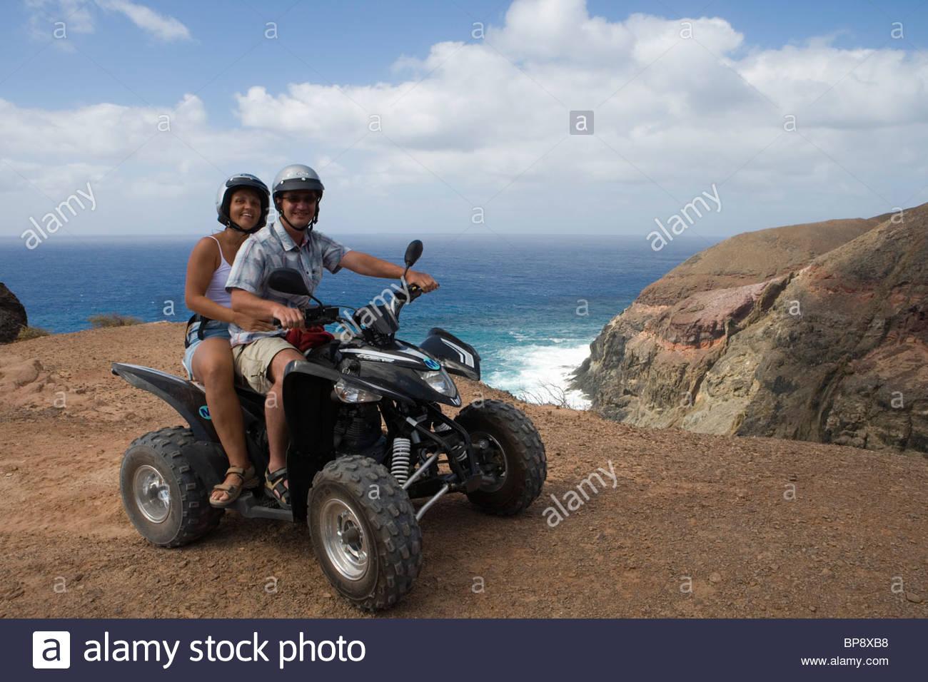 Couple on a quad all-terrain vehicle near Ponta da Canaveira, Porto Santo, near Madeira, Portugal - Stock Image
