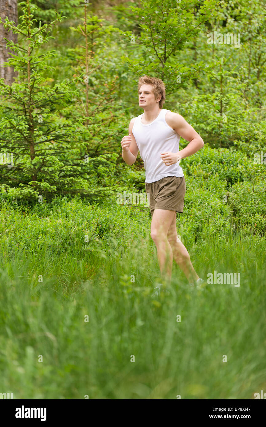 1ed7714ddca2 Young man jogging in nature in sportive outfit Stock Photo: 30929395 ...