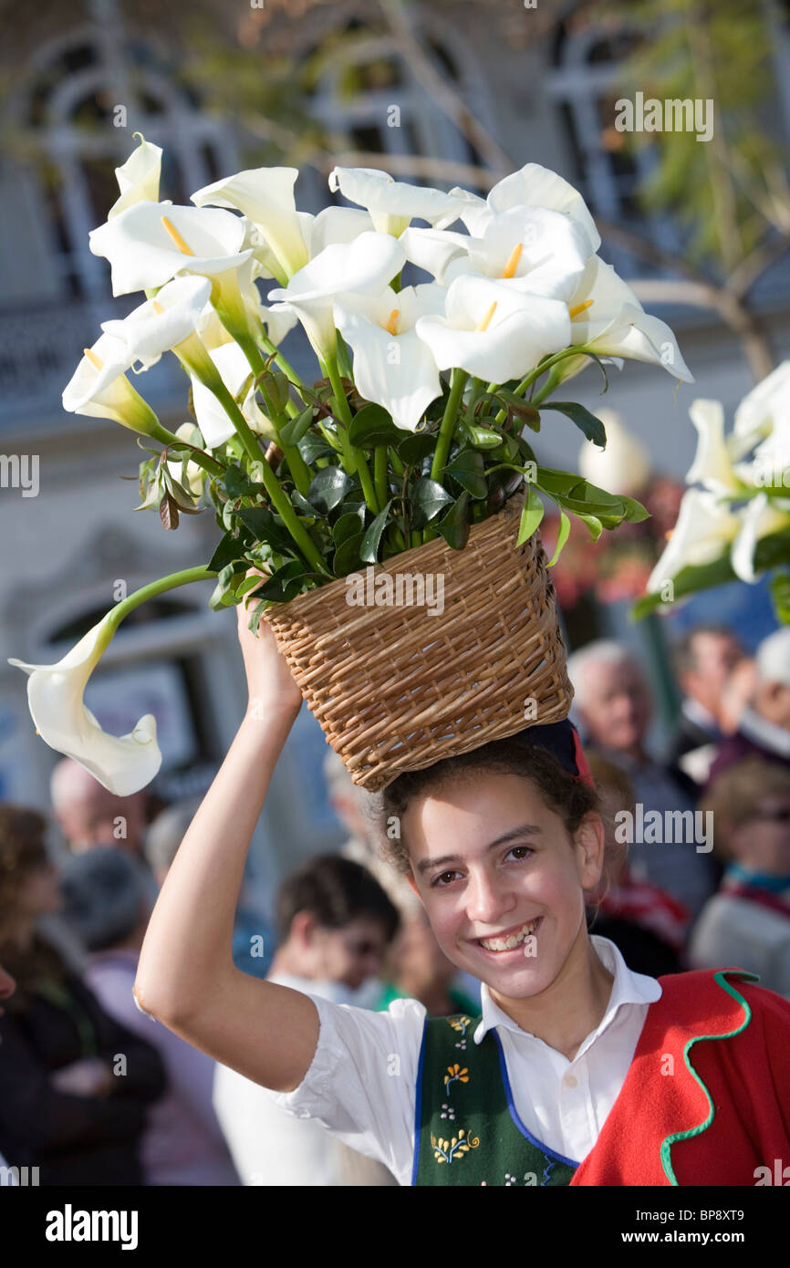 Young girl with basket of calla flowers ar the Flower Festival Parade, Funchal, Madeira, Portugal - Stock Image