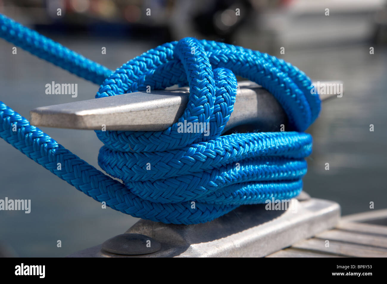 blue rope tied around a marina pontoon cleat in the uk - Stock Image