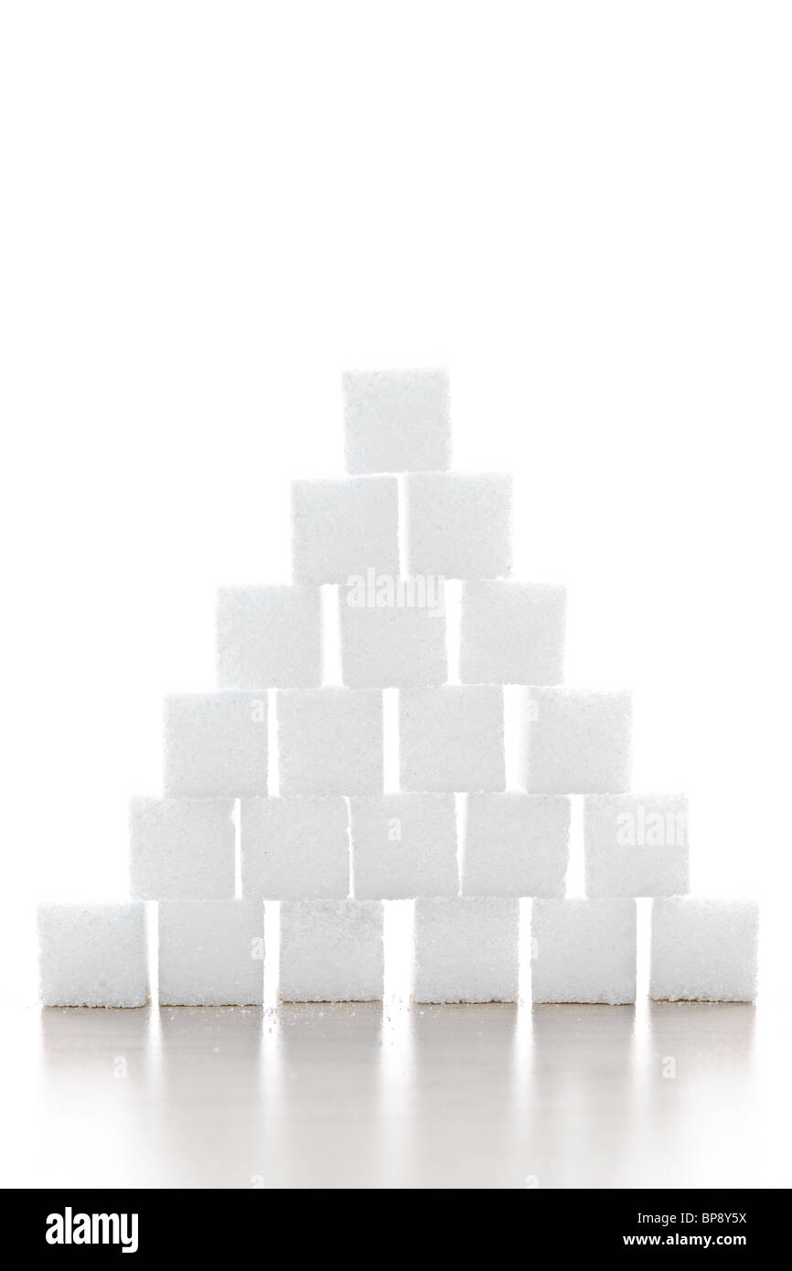 Pyramid of white sugar cubes stacked up on white background - Stock Image