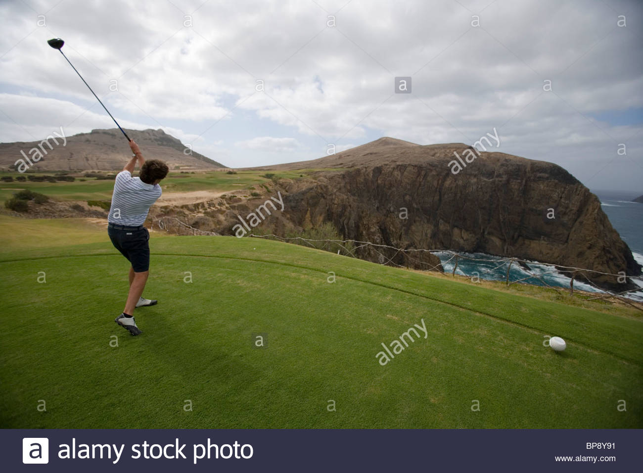 Golfer tees off at hole 14 at Porto Santo Golfe Golf Course, Porto Santo, near Madeira, Portugal - Stock Image