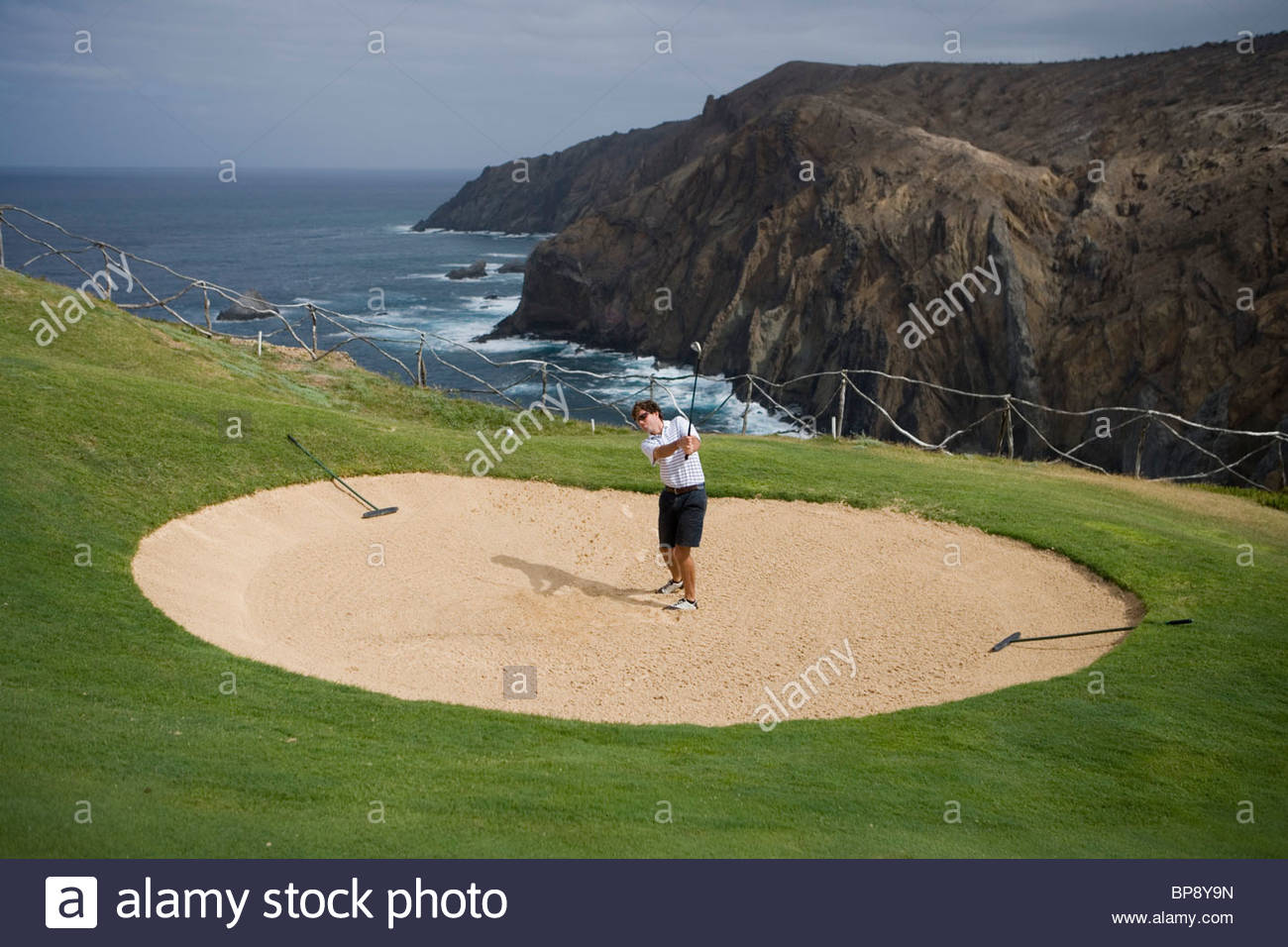 Golfer chips ball from sandtrap of hole 13 at Porto Santo Golfe Golf Course, Porto Santo, near Madeira, Portugal - Stock Image