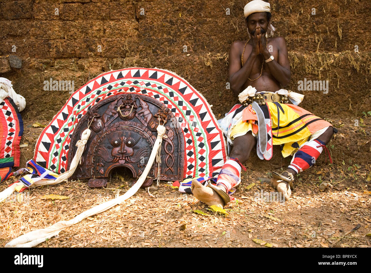 A Theyyam dancer rests by his headdress after perfoming in Kerala, India. - Stock Image