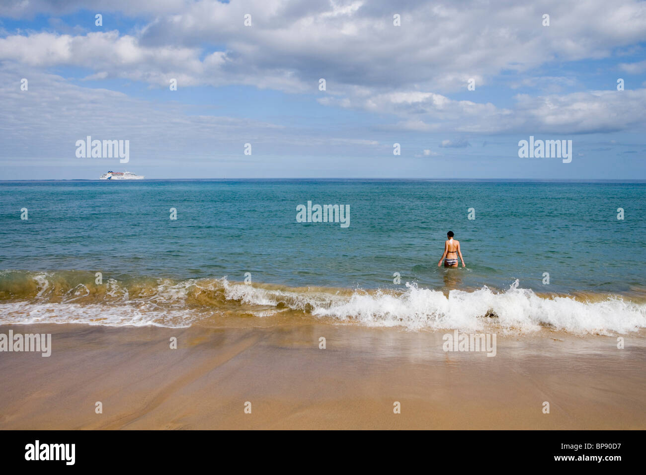 Woman going for a swim on Porto Santo Beach with Porto Santo Line Ferry Lobo Marinho on the horizon, Porto Santo, - Stock Image